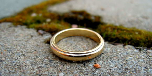 Abandoned wedding ring next to separation in ground symbolizing Alabama Divorce Property Settlement