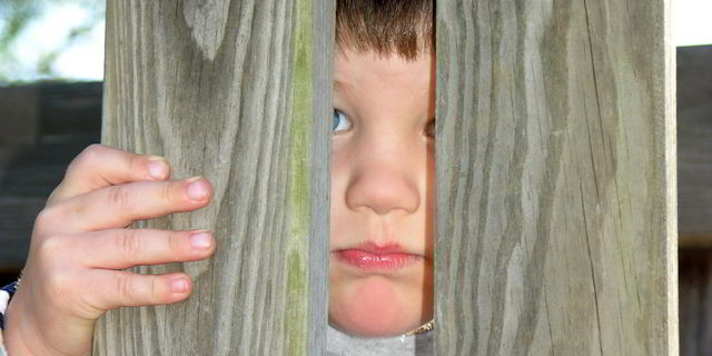 Sad boy peeking through wooden fence