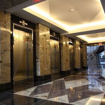 Elevator access in the marble and granite-lined foyer