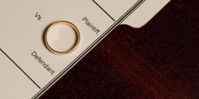"Wedding band resting on folder labeled ""Plaintiff vs. Defendant"""