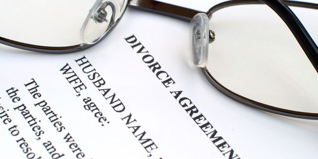"Eyeglasses resting on divorce agreement with words ""Husband name, Wife agree, the parties were..."""